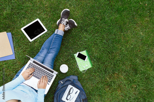 Foto  Top view of woman with laptop sitting on the green grass