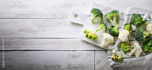 Cauliflower, romanesco broccoli and sicilian broccoli on white wood background