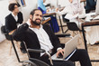 Disabled arab man in wheelchair working in office. Man's neck hurts.
