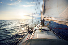 View From A Deck Of A Tilted Yacht In Strong Wind At Sunset. Clear Sky With Glowing Golden Clouds. Transportation, Nautical Vessel, Cruise, Sport, Regatta, Recreation