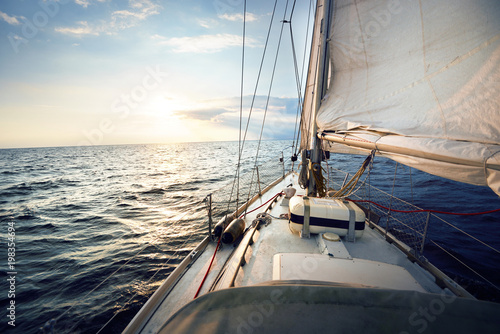 View from the deck to the bow of a sail yacht tilted in a wind on a sunset Fototapeta