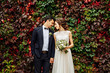canvas print picture - groom and bride posing in front ol old brick wall with ivy