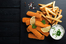 Fish Fingers And Fries With Sauce On Dark Background. Top View.