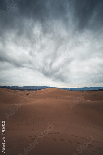 Huge sand dune with moody clouds above in the desert near Death Valley National Park, California USA