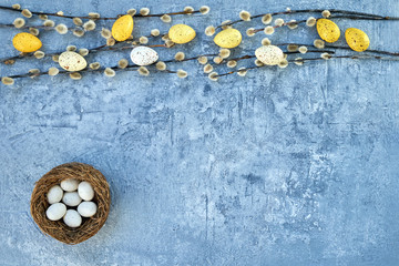Easter background. Willow branch and decorative Easter eggs on blue background. Top view, copy space