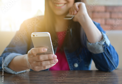 A brunette girl in a denim jacket is eating lunch in a cafe and using her phone. Communication through messenger. Smartphone. Casual loose clothing.