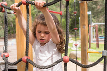 Little Girl Concentrating On Climbing Rope Frame At Playground In Natural Bushland Setting (selective Focus)
