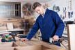 Worker chiseling plank at workshop