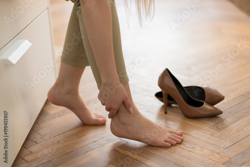 Tired woman touching her ankle, suffering from leg pain because of uncomfortable shoes, feet pain wear high heel shoes after work or walk, selective focus Canvas Print