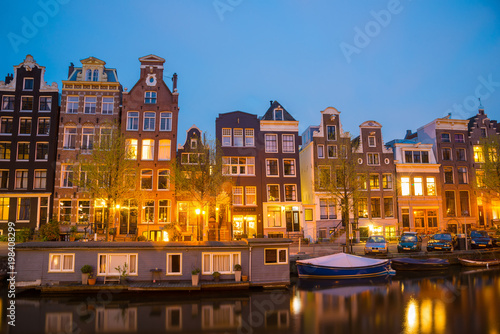 Poster Amsterdam Night view of Amsterdam cityscape with canal, bridge and houses in the evening