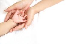 小さな赤ちゃんの手を母が両手で包むイメージ