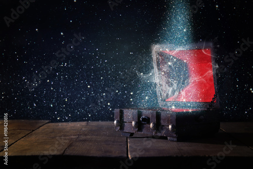 Image of mysterious treasure chest with glitter light and smoke over wooden old table Wallpaper Mural