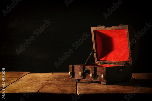 Photo  Image of empty mysterious treasure chest over wooden table.