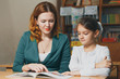 Female private tutor helping young student with homework at desk in bright child's room