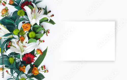A beautiful floral arrangement with white lilies and an empty sheet of paper for congratulations. A bouquet of flowers on a white background with copy space.