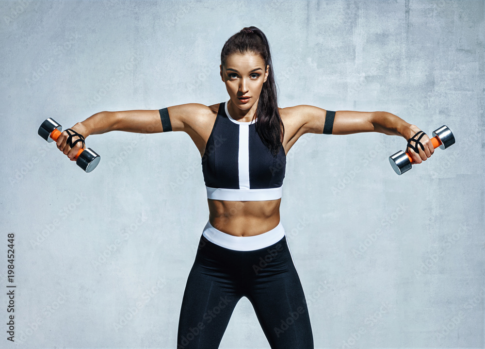 Fototapety, obrazy: Athletic woman doing exercise for arms. Photo of muscular fitness model working out with dumbbells on grey background. Strength and motivation