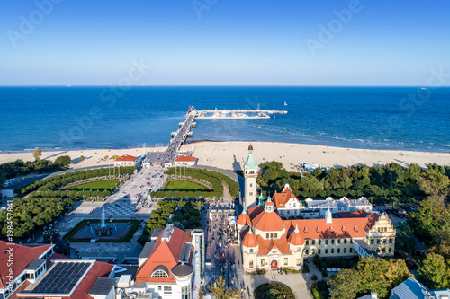 Sopot resort in Poland. SPA , old lighthouse, wooden pier (molo) with marina, yachts,  beach,  vacation infrastructure, park, promenade and walking people.  Aerial view.