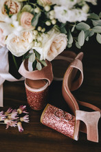 Wedding Velvet Pink Shoes With Shiny Beautiful Heels With Gold Wedding Rings Beside A Bouquet Of White Roses, Eucalyptus On A Dark Wooden Background