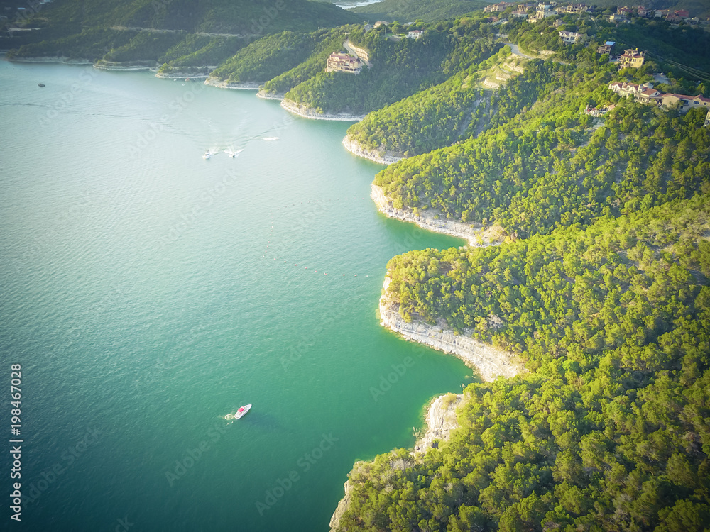 Vintage aerial trees and cliff rock wall, bluffs at Lake Travis, Austin, Texas, USA. Luxury vacation homes and house on coastline. Looking down houses in community, boats, ocean crystal background