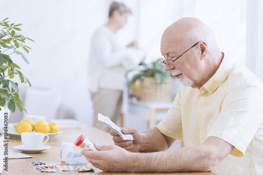 Fototapety, obrazy: Man reading his medicines' prescription