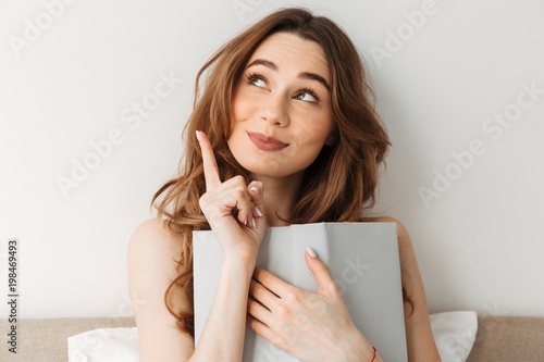 Fototapeta Portrait of cute relaxed woman 20s lying in cozy bed after sleep at bedroom, and reading book with interest obraz
