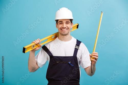 Fotografie, Obraz Happy male builder in protective helmet holding level tool
