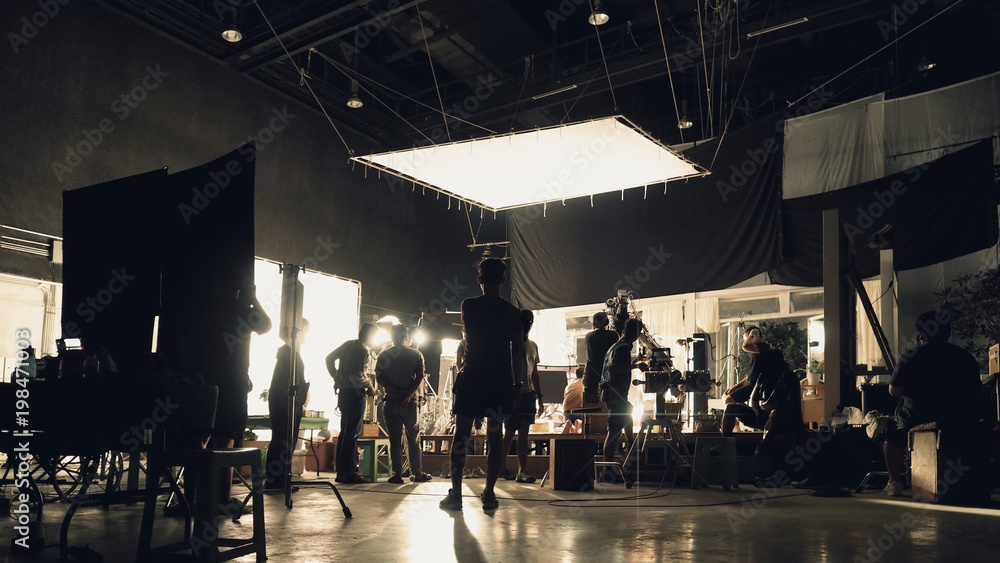 Fototapety, obrazy: Behind the scenes of silhouette people working in big production studio with professional set and lighting for making movie film or video commercial.