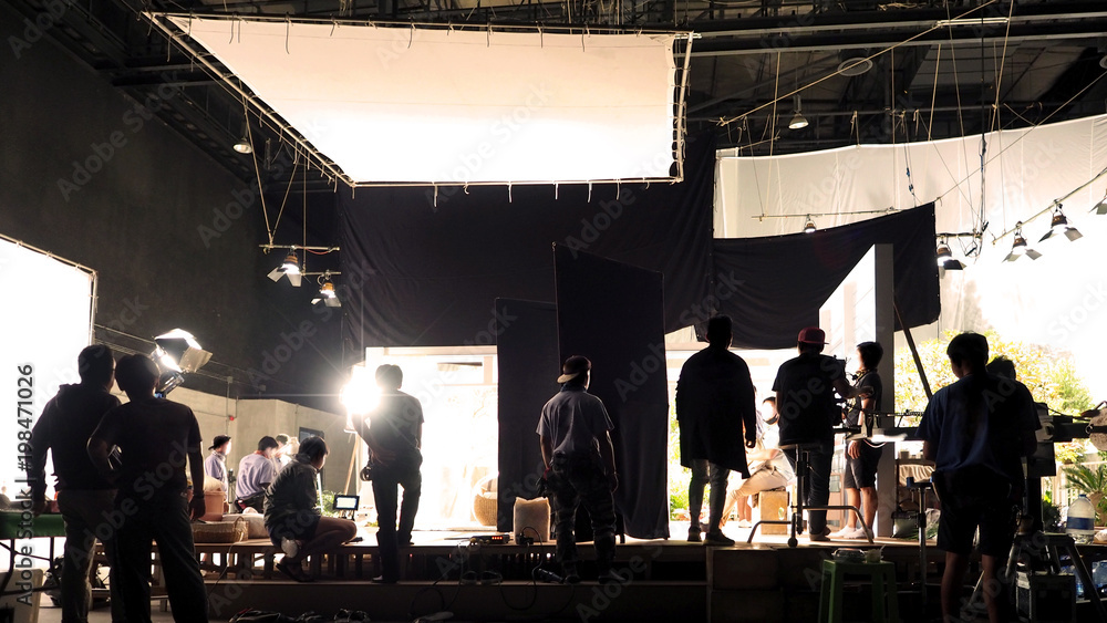 Fototapety, obrazy: Silhouette of people working in big production studio with professional equipment such as lighting, soft box, set and film crew team for filming or shooting movie TV or video commercial