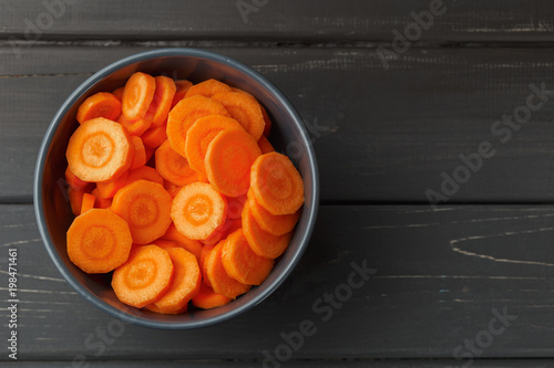 Sliced carrots in a bowl on black background