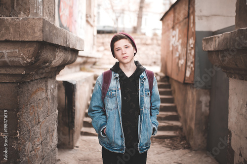 Stylish teen boy 14-16 year old posing at slum street. Sad emotions. Abandoned teenager.