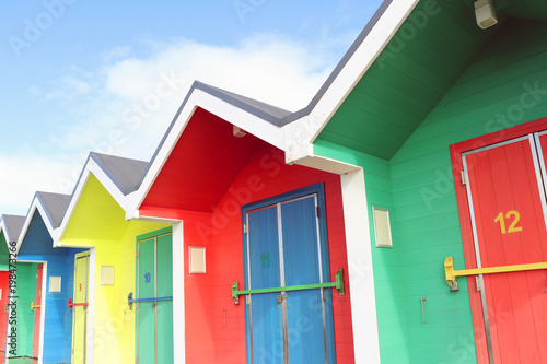 Fotografia  Colourful Beach Huts with Blue Sky in Background
