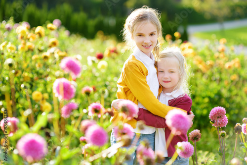 Cadres-photo bureau Dahlia Two cute sisters playing in blossoming dahlia field. Children picking fresh flowers in dahlia meadow on sunny summer day