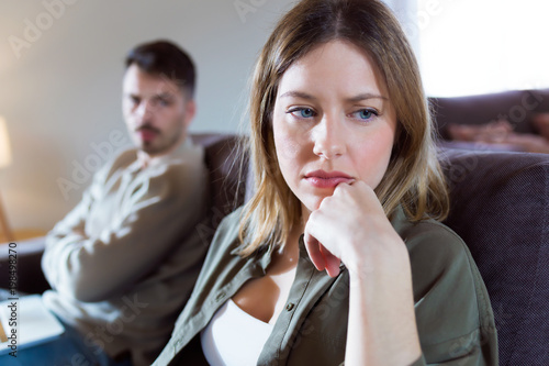 Vászonkép Offended young woman ignoring her angry partner sitting behind her on the couch at home