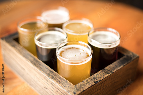 Photo Close up on a flight of craft beers in a wood sampling tray
