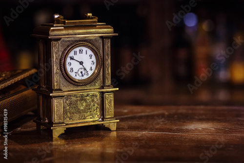 Fotografie, Obraz antique clock stand on a wooden table