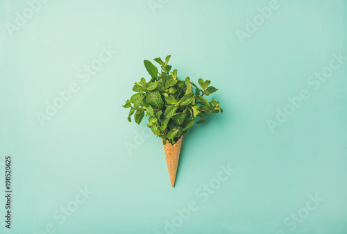 Flat-lay of sweet waffle ice-cream cone with bunch of fresh green mint over pastel mint background, top view. Spring or summer mood concept