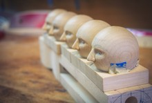 Wooden Doll Heads In A Row