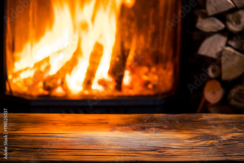 Fotografia, Obraz Old wooden table and fireplace with warm fire at the background.