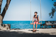 """Young man sits on a rope swing on sandy shore against blue sea and clear sky. Asian man wears T-shirt with """"Swinging"""", """"69"""" written on it, flip-flops, backback & watch on his arm. Ko Samet, Thailand"""