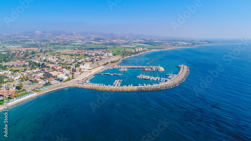 Photo Stands Port Aerial bird's eye view of Zygi fishing village port, Larnaca, Cyprus. The fish boats moored in the harbour with docked yachts and skyline of the town near Limassol city from above.