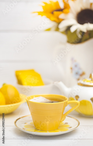 Deurstickers Thee Bright Yellow Tea Set on a White Wood Table