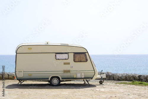Caravan on the sand beach with the blue sea on background Wallpaper Mural
