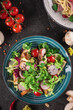 Fresh vegetable salad with grilled chicken breast - tomatoes, radish and mix lettuce leaves. Chicken salad. Healthy food. Black background. Top view