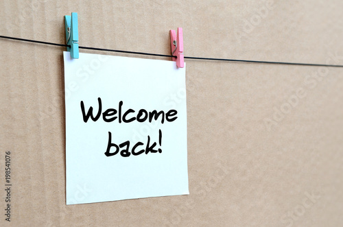 Photo  Welcome back! Note is written on a white sticker that hangs with a clothespin on
