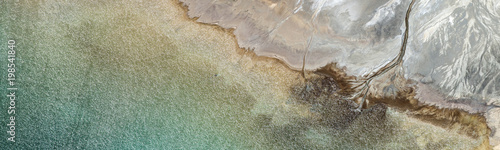 Aerial abstract panorama of colorful water streams at Los Leones Dam, filled with water of Nevado del Plomo, and the Los Leones and Blanco rivers