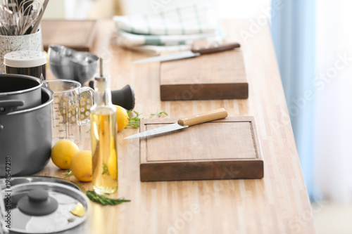 Poster Cuisine Cutting boards with kitchenware prepared for cooking classes on wooden table