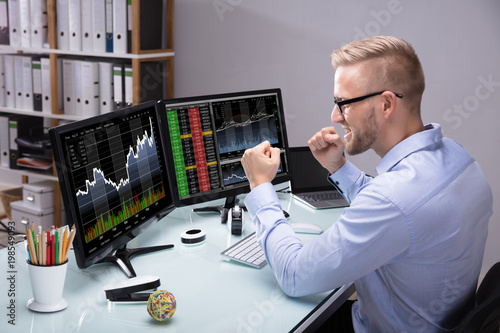 Fotomural Excited Stock Market Broker Looking At Graph On Computer