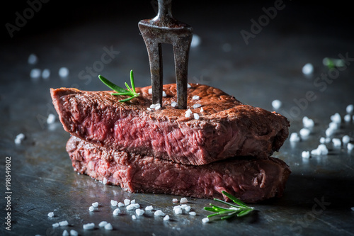 Photo Stands Steakhouse Closeup of medium rare steak with salt and herbs
