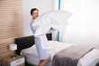 Female Housekeeper Carrying Pillows In Hotel Room
