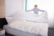 Housekeeper Arranging Bedsheet On Bed